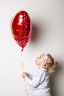 Little girl holding a heart air balloon and looks at it on a light background. concept for valentine's day, birthday. banner.