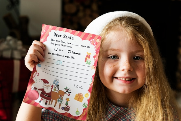 Little girl holding her christmas wishlist