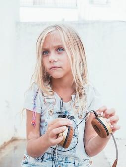 Маленькая девочка держит наушники