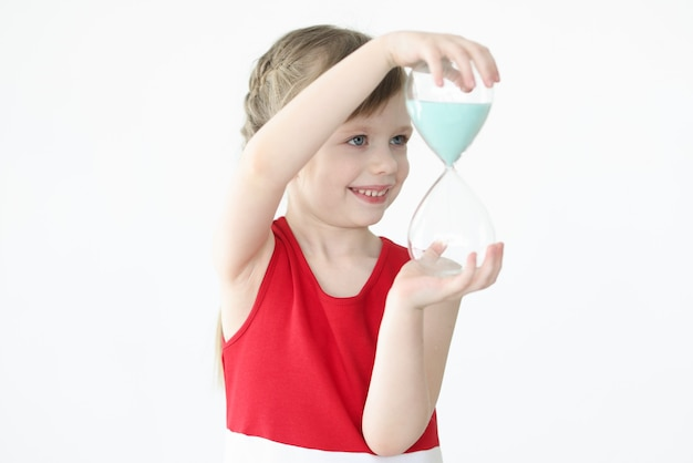 Little girl holding hourglass in her hands. sleep and rest in children concept