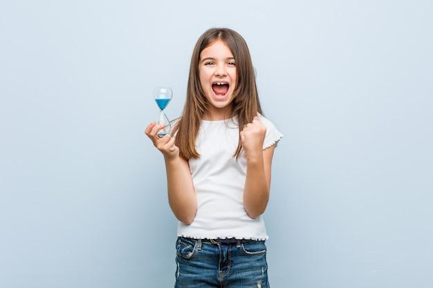 Little girl holding an hourglass