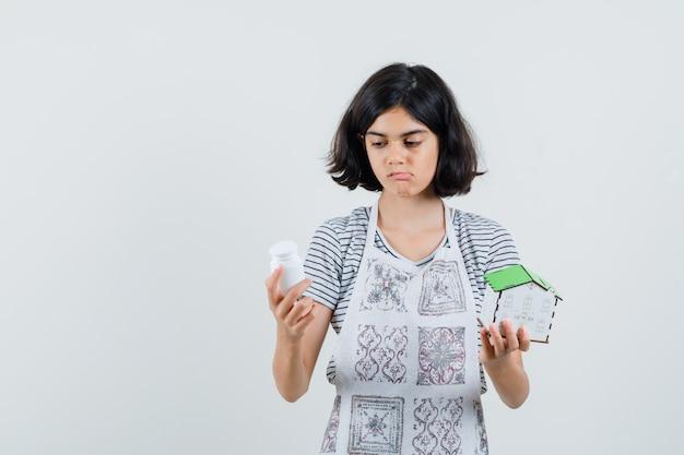 Bambina che tiene modello di casa, bottiglia di pillole in t-shirt, grembiule e sguardo esitante.
