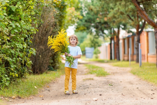 .little girl holding a huge bouquet of yellow autumn flowers in the field. golden autumn, indian summer, warm sunny weather in the countryside