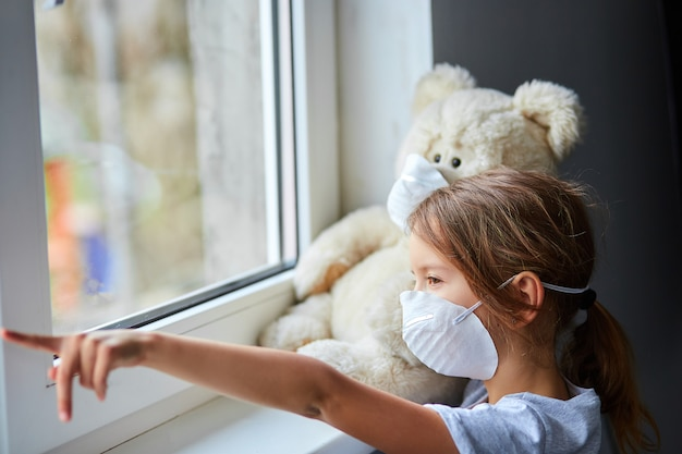 Little girl holding and hugging teddy bear in mask near the window. coronavirus, covid-19 and pollution protection concept. stay at home.