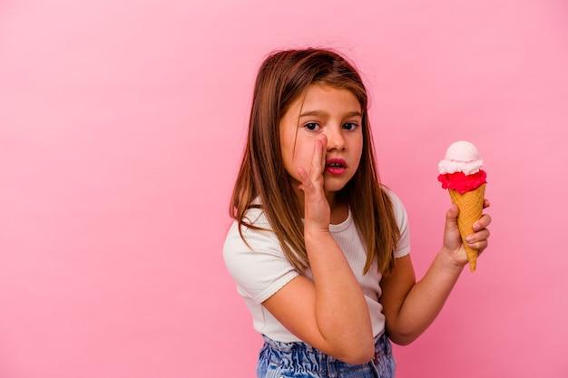 ピンクの壁に分離されたアイスクリームを保持している少女は、秘密のホットブレーキのニュースを言って脇を見ています