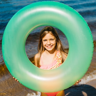 Маленькая девочка держит надувное плавательное кольцо
