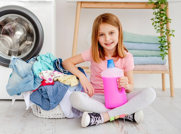Маленькая девочка держит жидкий гель для стирки, сидя на полу рядом с одеждой в корзине