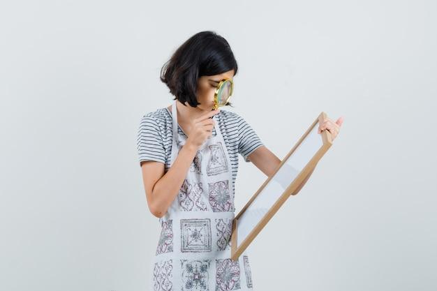 Bambina che tiene la lente d'ingrandimento sulla cornice vuota in t-shirt, grembiule