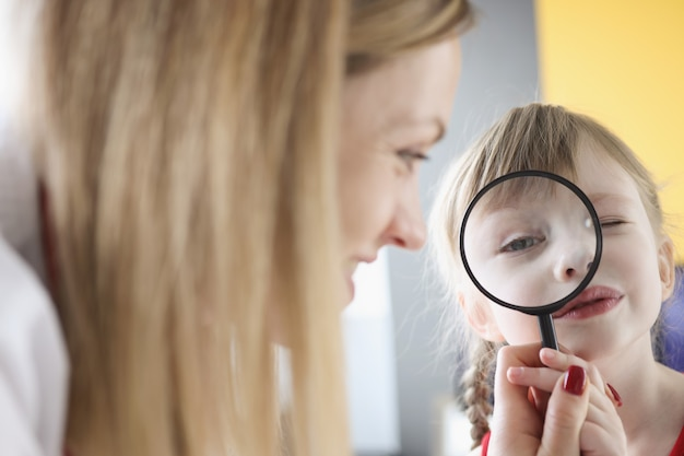 Little girl holding magnifying glass near eye next to her mother annual preventive medical