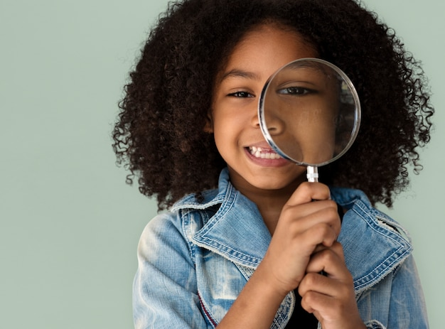 Little girl holding magnifying glass smiling