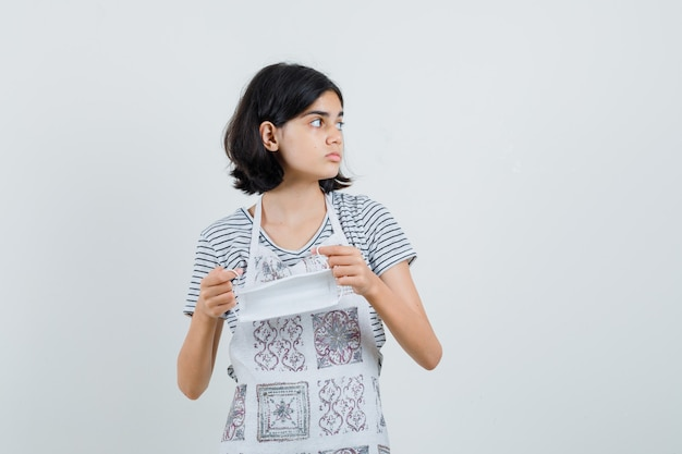 Bambina che tiene mascherina medica mentre osserva da parte in maglietta, grembiule