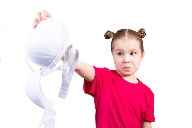 お母さんのブラジャーを手に持った少女。白い背景で隔離。あらゆる目的のために。