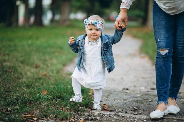 Little girl holding mother's hand in park