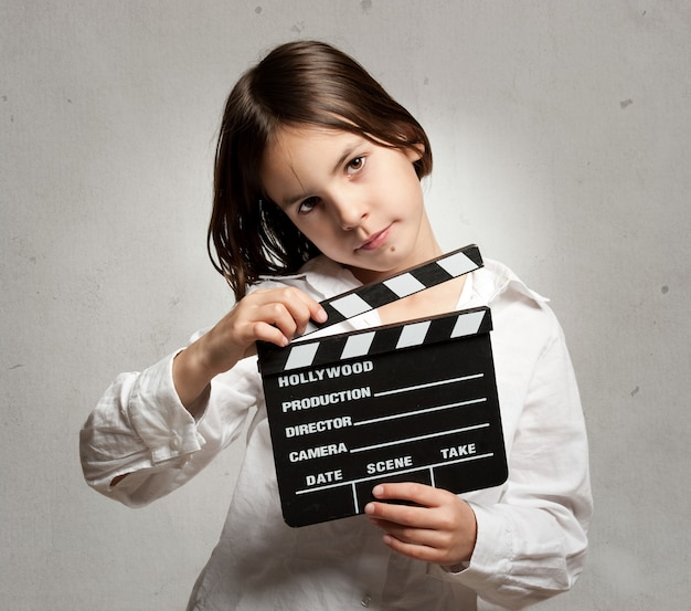 Little girl holding a movie clapper board on a grey background