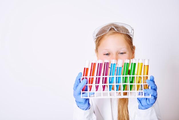 Маленькая девочка держит разноцветную лабораторную посуду