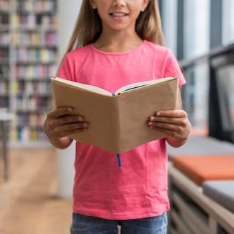 Bambina che tiene un libro aperto