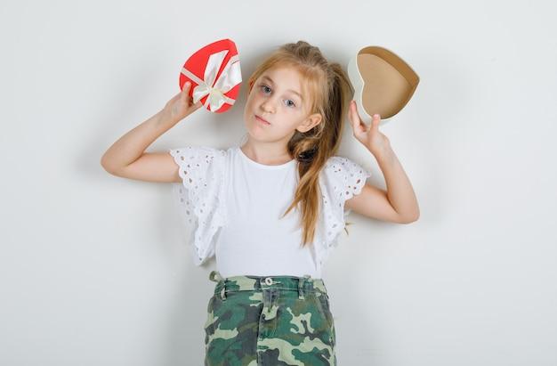 保持している小さな女の子が白いtシャツでプレゼントボックスを開く