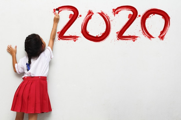 Little girl holding a paint brush painting happy new year 2020 on a white wall
