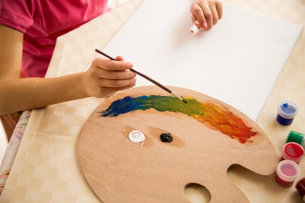 Маленькая девочка держит поддон и рисует на холсте масляными красками