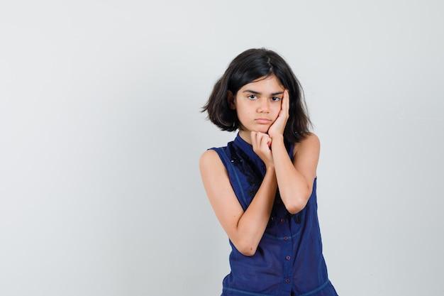 青いブラウスで頬に手のひらを持って悲しそうに見える少女。正面図。