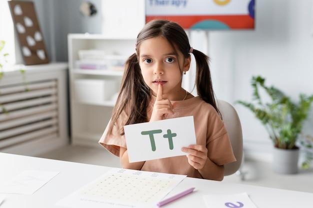 Bambina che tiene una carta con una lettera sopra nella logopedia