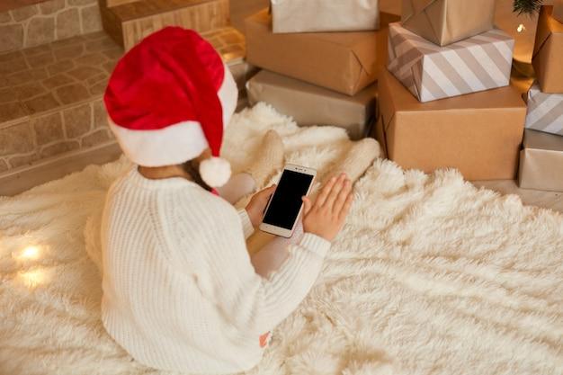 거꾸로 포즈를 취하는 동안 빈 화면으로 전화를 들고 어린 소녀 흰색 스웨터와 산타 모자를 쓰고, 부드러운 카펫에 바닥에 앉아.