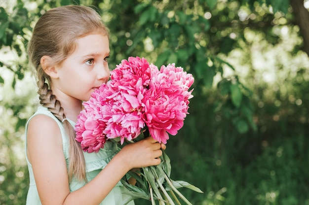 Little girl holding a pink peony flowers bouquet in her hands and smelling it