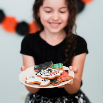 Little girl holding a plate with cookies