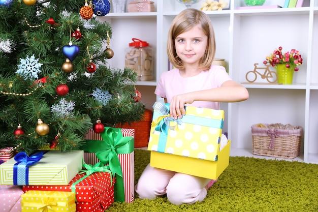 방에 있는 크리스마스 트리 근처에 선물 상자를 들고 있는 어린 소녀