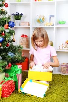 部屋のクリスマスツリーの近くにプレゼントボックスを保持している少女