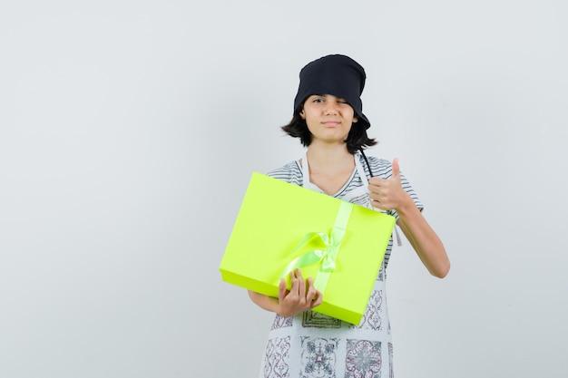 어린 소녀 선물 상자를 들고 부엌 드레스에 엄지 손가락을 보여주는