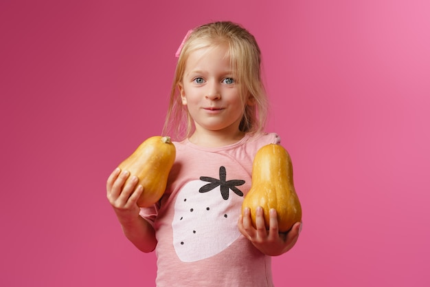 Маленькая девочка держит тыкву в руках