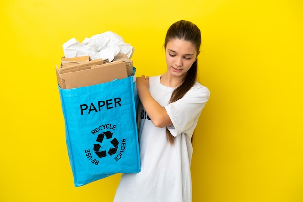 Little girl holding a recycling bag full of paper to recycle over isolated yellow wall suffering from pain in shoulder for having made an effort