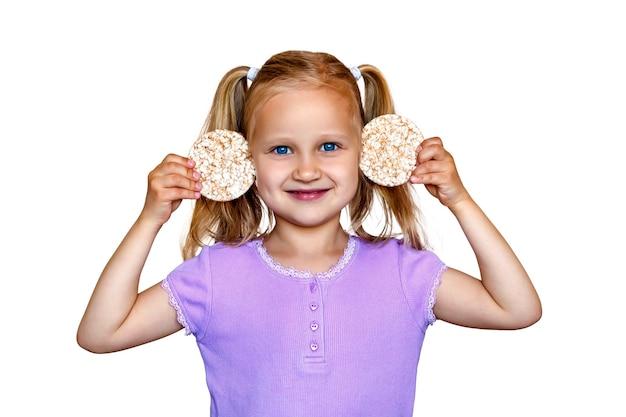 Little girl holding rice cookies near her ears