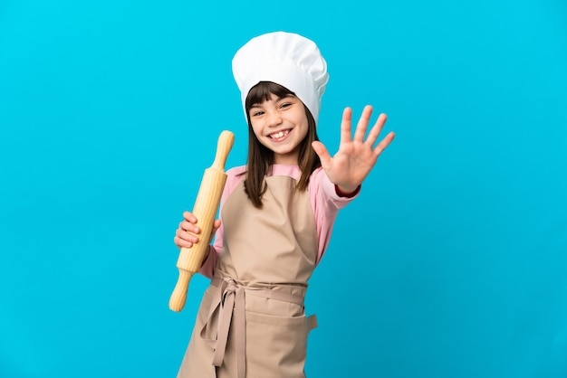 Little girl holding a rolling pin isolated on blue background counting five with fingers