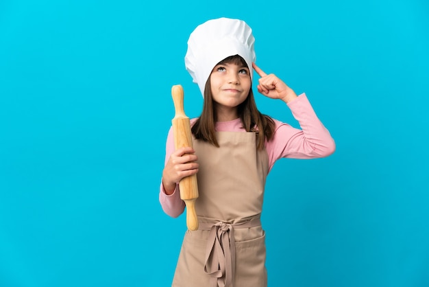 Little girl holding a rolling pin isolated on blue background having doubts and thinking