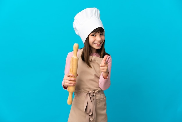 Little girl holding a rolling pin isolated on blue background surprised and pointing front
