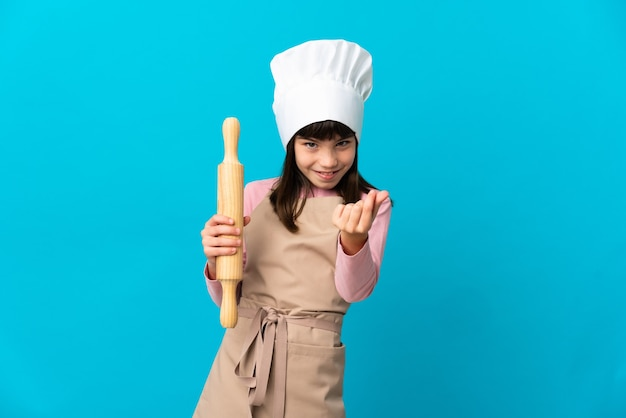 Little girl holding a rolling pin isolated on blue wall making money gesture