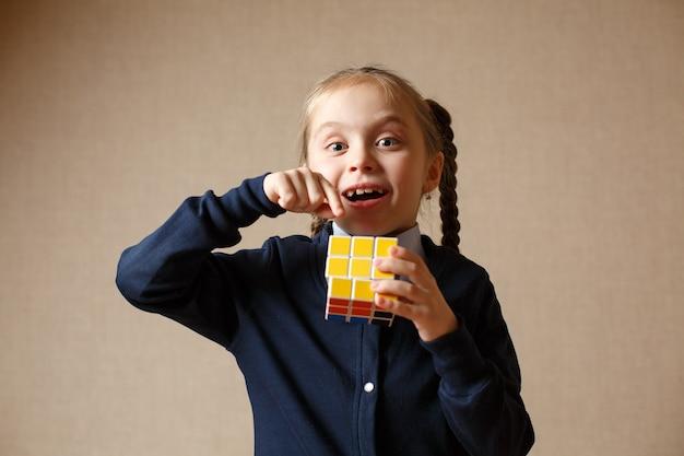 A little girl holding a rubik's cube