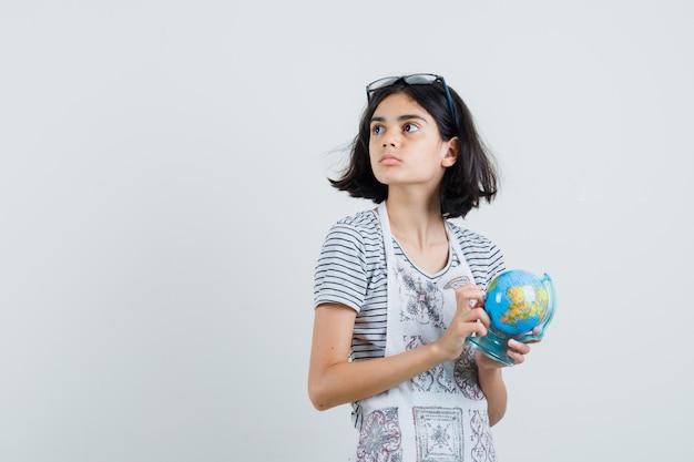Bambina che tiene il globo della scuola in maglietta, grembiule e che sembra pensieroso.