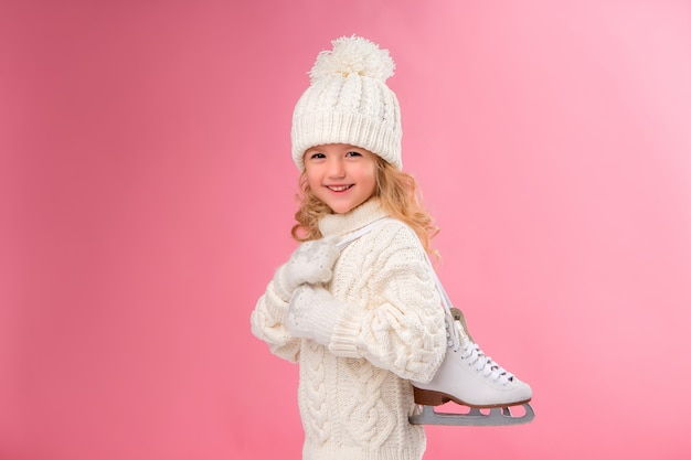 Little girl holding skates. isolate on pink wall, space for text.