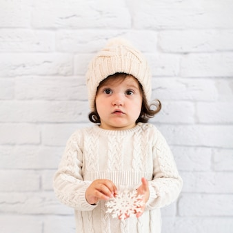 Little girl holding a snowflake and looking at photographer