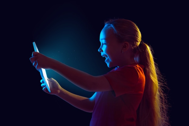 暗闇の中でタブレットを保持している少女