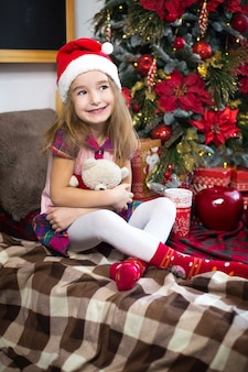 A little girl holding a teddy bear, sitting on a plaid blanket in the christmas decorations near a christmas tree with boxes of gifts and a santa hat. new year, children's game