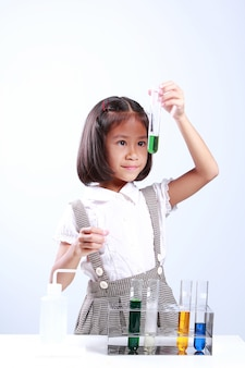 Little girl holding a test tube with liquid, scientist chemistry and science education con