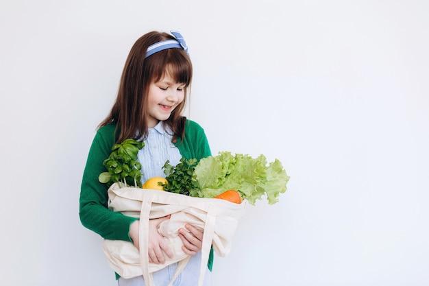 Маленькая девочка, держащая текстильный продуктовый мешок с овощами. концепция нулевых отходов. безпакетные покупки продуктов питания. экологичная натуральная сумка с органическими фруктами и овощами.