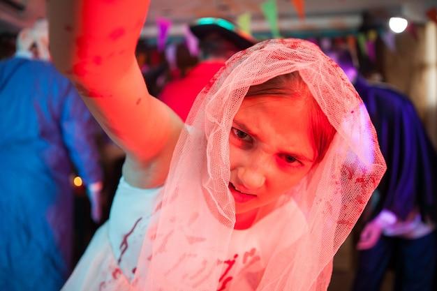 Маленькая девочка держит камеру, одетая в платье для прополки, залитое кровью, для хэллоуинского карнавала. жуткая девочка.