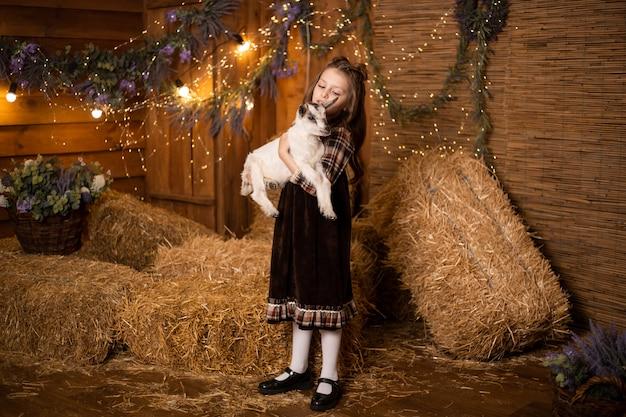 レトロなドレスを着ている干し草の背景に農場で小さなヤギを保持している少女