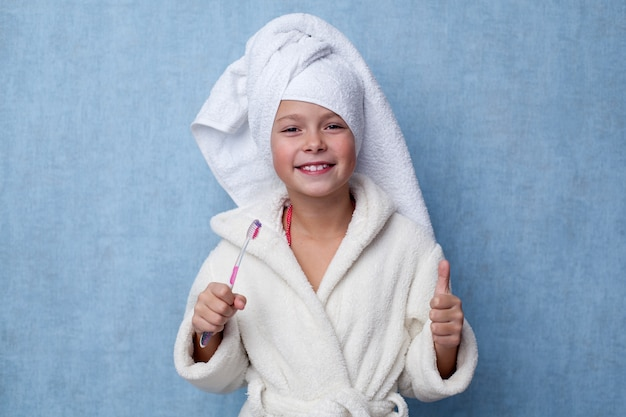Little girl holding a toothbrush in her hand and showing thumbs up gesture