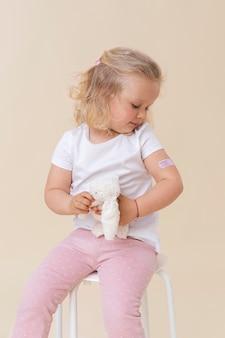 Маленькая девочка держит игрушку после вакцинации